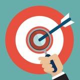 Main d'homme d'affaires avec la loupe sur la cible avec la flèche Photo libre de droits