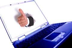 Main d'homme d'affaires dans le trou sur l'ordinateur portatif photographie stock
