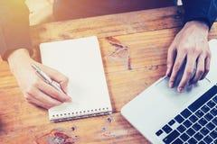 Main d'homme d'affaires de l'Asie utilisant l'ordinateur portable et le bloc-notes d'écriture sur le tabl Photos stock