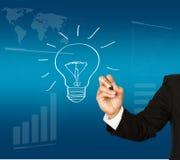 Main d'homme d'affaires dessinant l'ampoule Image stock