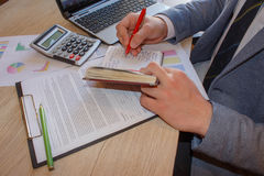 Main d'homme d'affaires fonctionnant avec le nouvel ordinateur moderne et écrivant sur le diagramme de stratégie de bloc-notes en photo libre de droits