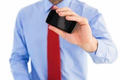 Main d'homme d'affaires montrant le smartphone Photo stock