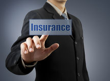 Main d'homme d'affaires poussant le bouton d'assurance Photographie stock