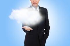 Main d'homme d'affaires retenant le nuage blanc Photo stock