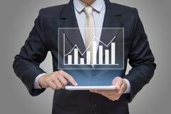 Main d'homme d'affaires tenant des finances de graphique de comprimé sur le fond gris Photo libre de droits