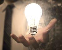 Main d'homme d'affaires tenant l'ampoule avec la lumière lumineuse Photos stock