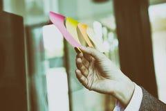main d'homme d'affaires tenant la note de papier collante vide sur la fenêtre i Images libres de droits
