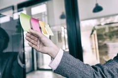 main d'homme d'affaires tenant la note de papier collante vide sur la fenêtre i Images stock