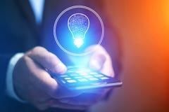 Main d'homme d'affaires tenant le téléphone portable avec l'icône d'idée d'ampoule Images stock