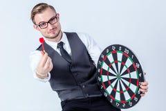 Main d'homme d'affaires tenant une cible avec des dards frappant le centre Image libre de droits