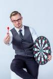 Main d'homme d'affaires tenant une cible avec des dards frappant le centre Photos stock