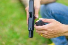 Main d'homme d'arme à feu sur le fond vert images stock