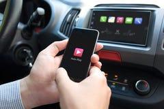 Main d'homme dans le téléphone de participation de voiture avec des multimédia automatiques de jeu photographie stock libre de droits
