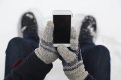 Main d'homme dans les gants de laine tenant le téléphone intelligent d'écran vide clos photographie stock