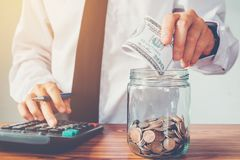 Main d'homme de concept d'argent d'économie mettant la rangée et la calculatrice fi de pièce de monnaie photo libre de droits