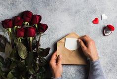Main d'homme de jour de valentines tenant la lettre d'amour d'enveloppe avec la carte de voeux Images libres de droits