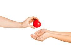Main d'homme donnant le coeur rouge à la femme Photo stock