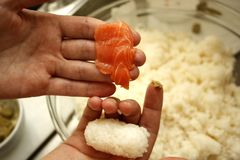 Main d'homme préparant des sushi de nigiri de riz et thons et wasabi photo stock
