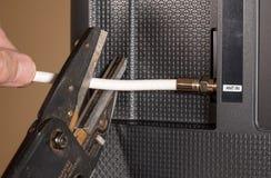 Main d'homme supérieur coupant la corde sur son paquet TV par câble Images stock