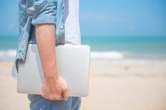 Main d'homme tenant l'ordinateur portable à la plage Photographie stock