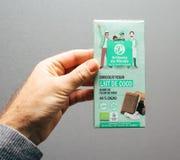 Main d'homme tenant le chocolat de Vegan d'Artisans du Monde Photos libres de droits