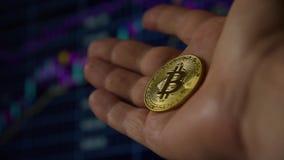 Main d'homme tenant un bitcoin de pi?ce d'or banque de vidéos
