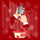 Main d'hommes d'achats de Noël tenant le téléphone portable moderne Photo stock