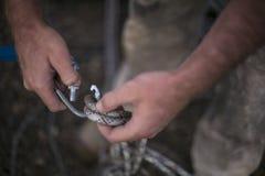 Main d'inspecteur d'accès de corde inspectant la coupure fermant à clef des karabiners dedans à descendre en rappel la corde images stock