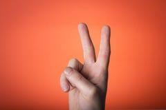Main d'isolement sur le fond de rouge orange Photos stock