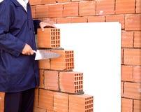 Main d'ouvrier étendant des briques Images libres de droits