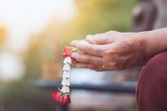 Main d'un aîné plus âgé tenant de belles guirlandes de fleur Photos stock