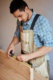 Main d'un charpentier prenant la mesure d'une planche en bois image stock