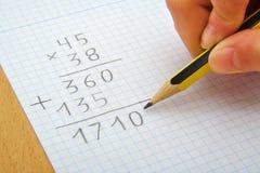 Main d'un enfant faisant une multiplication avec a Image libre de droits