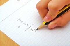 Main d'un enfant faisant une somme maths école de copyspace de concept de livres noirs de fond Photographie stock