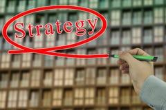 Main d'un homme d'affaires tenant un stylo vert écrivant un tex de stratégie Photo libre de droits