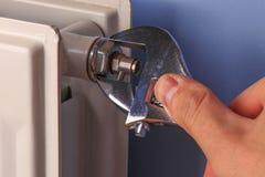Main d'un homme, dépanneur, plan rapproché de valve de radiateur d'installation photo libre de droits