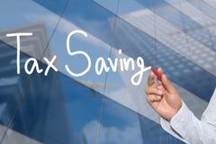 Main d'un homme d'affaires tiré par la main un mot de l'économie d'impôts Photo libre de droits