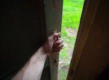 Main d'un homme ouvrant la vieille trappe Image libre de droits