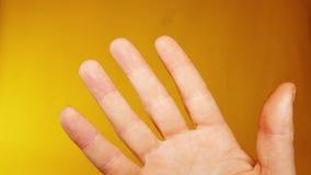 Main d'un homme sur un fond jaune, idéal de longueur pour représenter les parties mal allées et les situations comiques photographie stock libre de droits