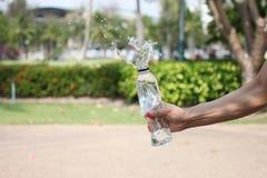 Main d'un homme tenant une bouteille d'eau potable  photo stock