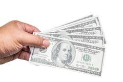 Main d'un homme tenant une poignée éventée de 100 dollars Image stock