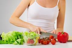 Main d'une femme au foyer de femme préparant le dîner Image libre de droits