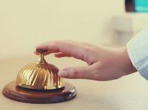 Main d'une femme employant une cloche d'hôtel Images stock