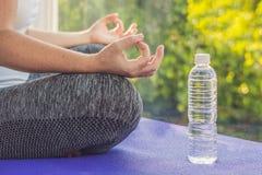 Main d'une femme méditant dans une pose de yoga sur une couverture pour le yoga et une bouteille de l'eau Photo libre de droits