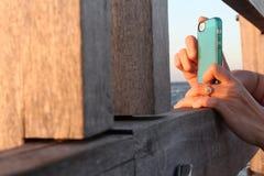 Main d'une femme prenant la photo utilisant son téléphone portable Image libre de droits