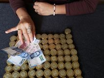 main d'une femme tenant les billets de banque mexicains et les pi?ces de monnaie empil?es de dix pesos mexicains image stock