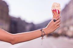 Main d'une jeune femme agréable tenant la crème glacée  image libre de droits