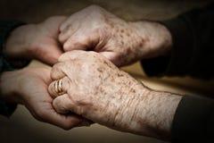 Main d'une jeune femme secouant cela d'un aîné Photographie stock libre de droits