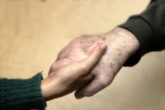 Main d'une jeune femme secouant cela d'un aîné Photos libres de droits