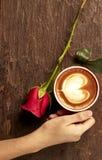 Main d'une jeune femme tenant une tasse de café rouge Images libres de droits